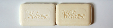 Strip taken from larger photograph. Shows two handsoaps next to each other, both cream, one slightly lighter than the other. They both say 'Welcome' on them.
