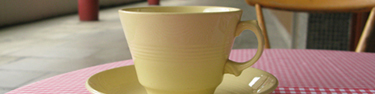 Strip taken from larger photograph. Shows a yellow tea cup sitting on a round table, covered in a red gingham table cloth.