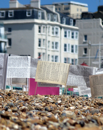 Photograph of paper flags made from pages of books, stuck in the shingle on Brighton beach.