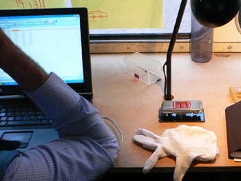 Image showing the elbow of a man working on a laptop at a desk. To his right, benath a black angle poise lamp is a small grey toy car, and a white glove.