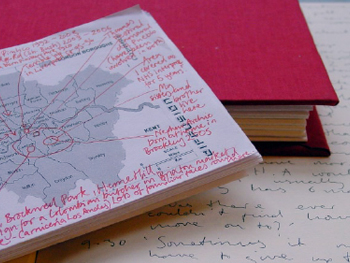Photograph of an annotated map of London, resting against a red hardback book, on the pages of a notebook which has been written on.