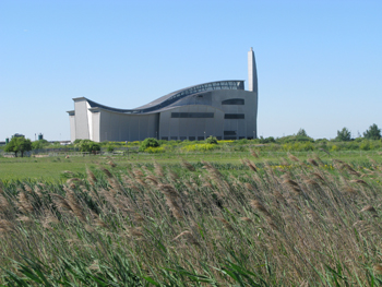 Photograph of a shiny silver building with a curved roof. In the foreground is green marshland.