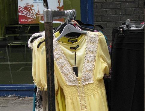 Photograph shows a yellow dress hanging on a clothes rail in a street market.