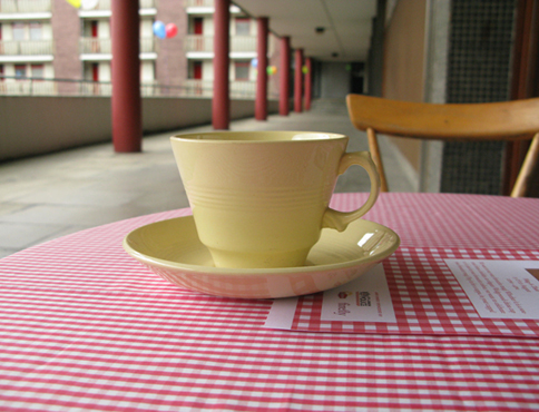 Photograph showing a yellow tea cup sitting on a round table, covered in a red gingham table cloth. There is a wooden chair in the middleground to the right. To the left are a series of red pillars and a block of flats in the distance.