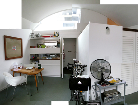 Photographic montage of the interior of a flat. In the foreground is a fan on a metal trolley, and a bicycle leaning agains a white wall. In the mid ground to the left is a white chair and a wooden table. In the background up high, is a large arched window letting light in.