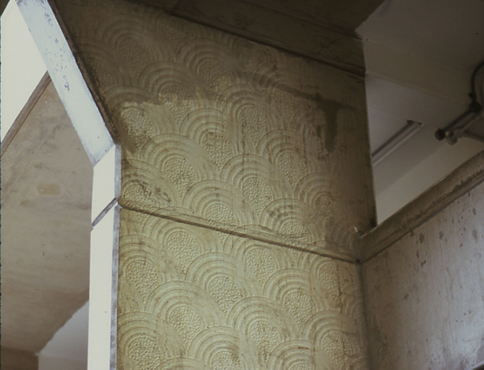 Photograph showing scallop wallpaper patterns projected on to a a large, flat concrete pillar.
