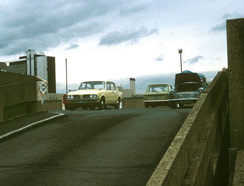 Photograph showing thee classic cars on the top deck of a multi storey car park. The picture is taken from the ramp leading up to the car park.