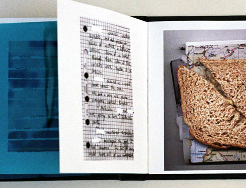Photograph of the book 'point and place'. The book is open and pages are turning from left ro right. The left page is blue, the turning page has a scan from a notebook on it, the page to the right has an image showing a sandwich with maps as a filling.