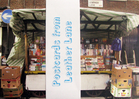 Photograph of the postcard publication 'Postcards From Leather Lane'. It features the picture of the bookstall, plus the title in blue on a paper band running vertically across the middle.