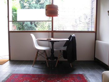 A table and two chairs are infron of a large window which looks out on to the garden. There is a jacket on the chair on the right. There is a red carpet in the foreground, and a wooden lampshade hangs above the table.