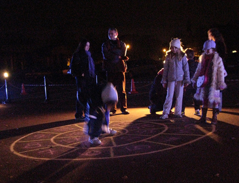 Family playing hopscotch at night