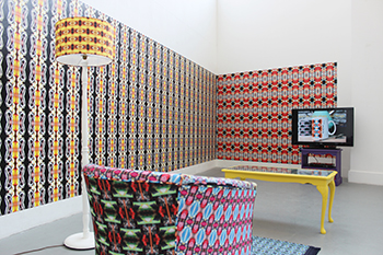 A shot of an installation with a brightly patterned armchair and standard light, with patterned wall paper on the walls and a TV
