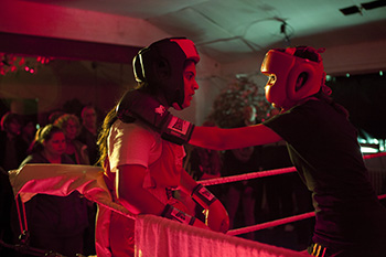 An atmospheric show of two female boxers in a boxing ring. Lit by red light.
